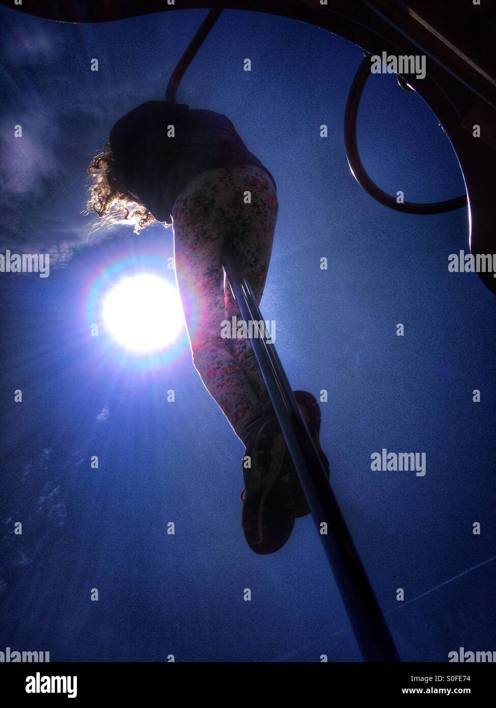 Young girl sliding down pole on playground backlit by sun - Stock Image