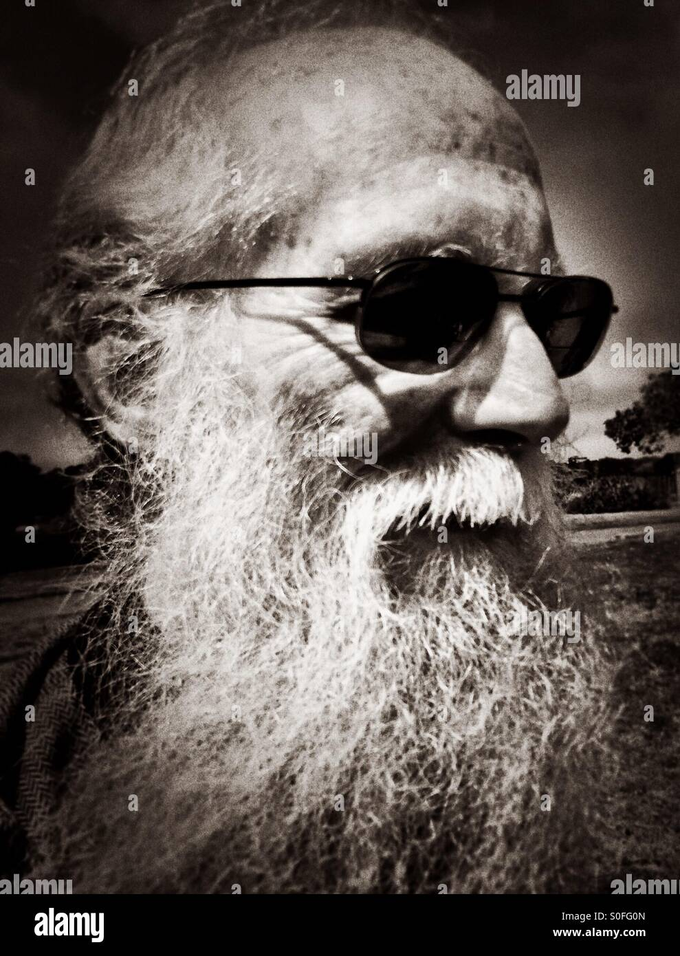 c28fa7599c38 Portrait of an elderly gentleman with long white beard and sunglasses.  Black and white vignette
