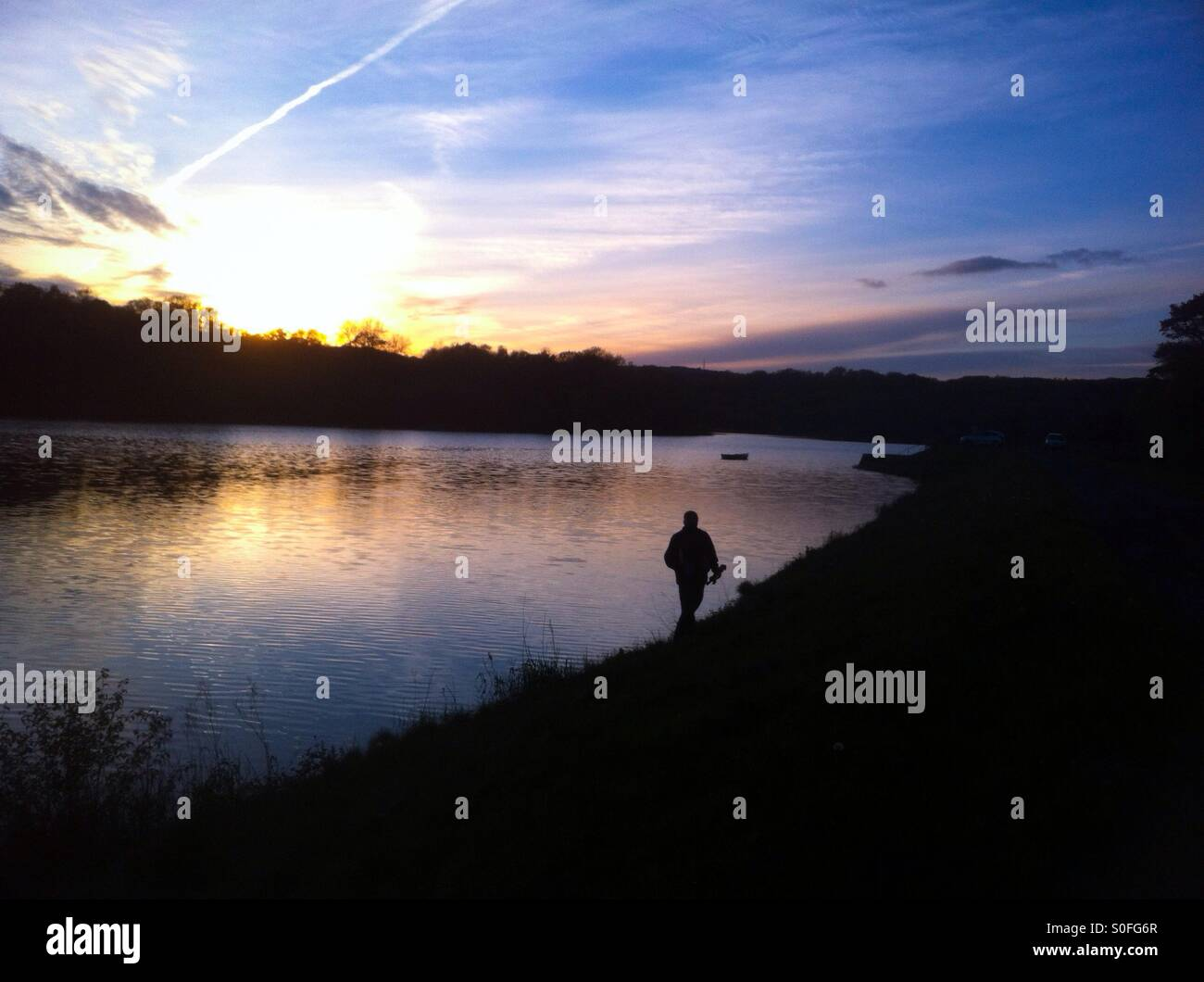 Man walking along the edge of a reservoir at sunset, Llanelli, Wales - Stock Image