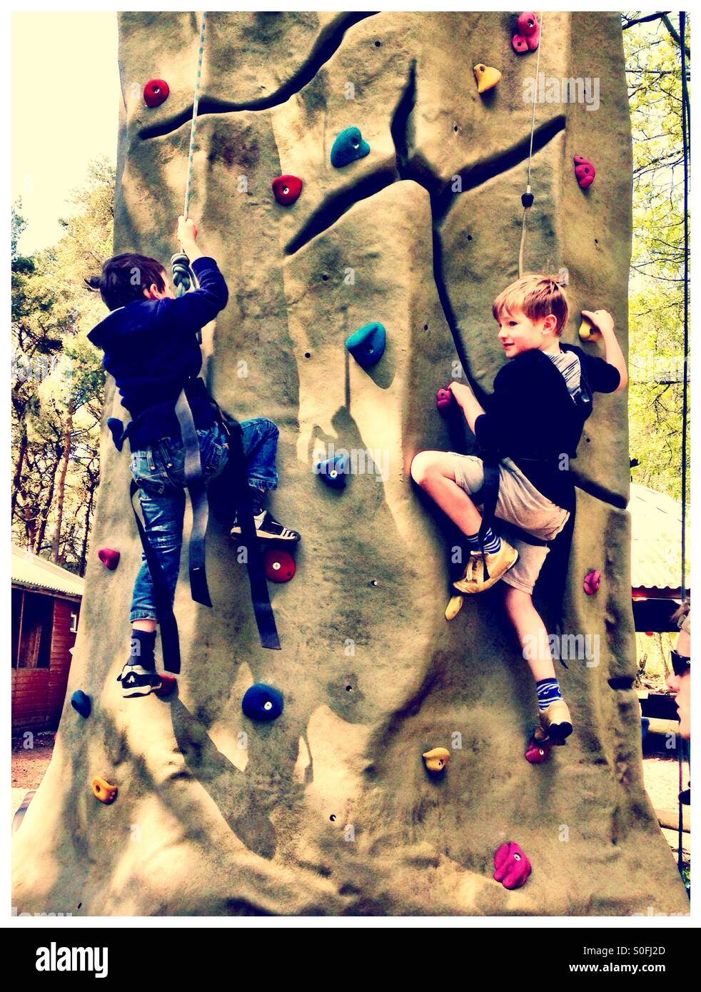 Two boys on a climbing wall. Adventure activity. - Stock Image
