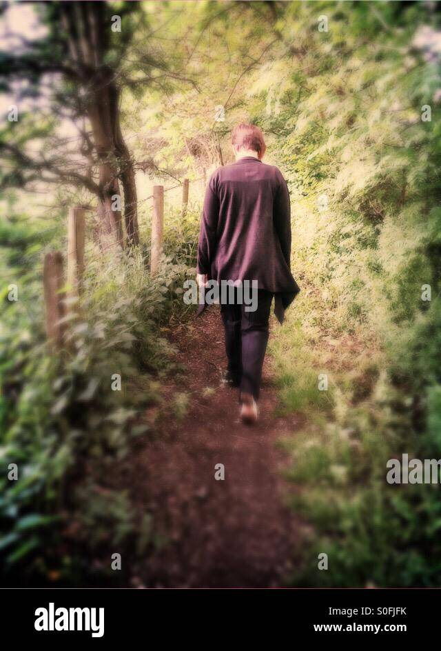 Walking deep in thought along the woodland path - Stock Image