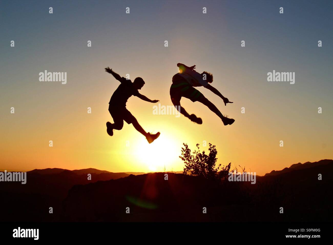 Jumping for joy as they find lighting better than they'd hoped for - Stock Image