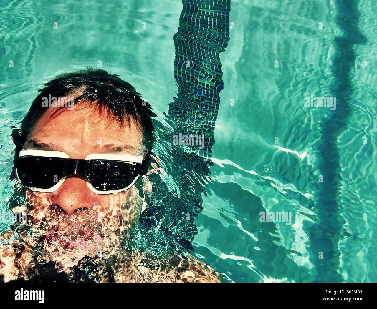 The swimmer. Top view above man swimming backstroke in an outdoor pool. - Stock Image