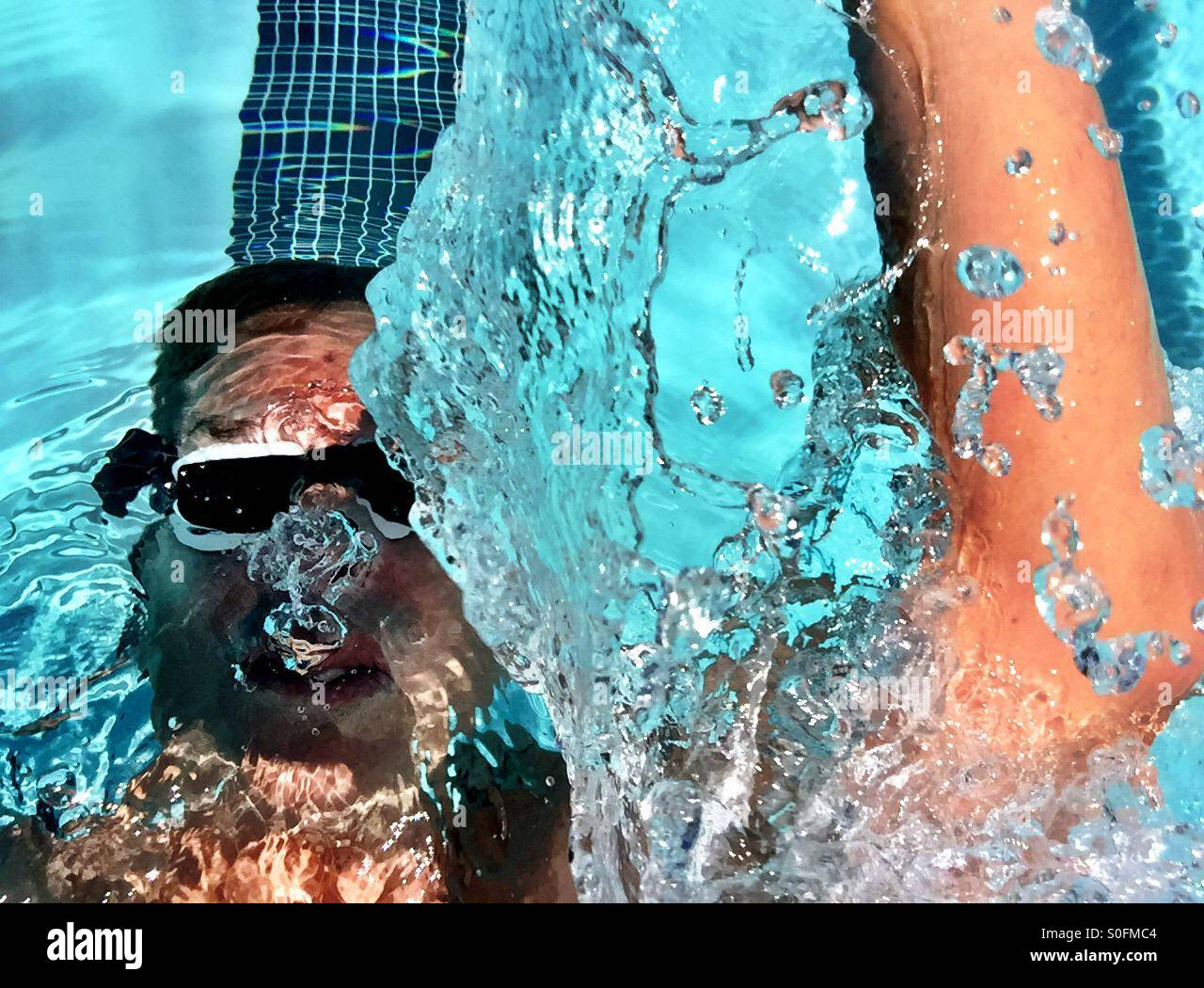 Closeup top view above water splash from male swimmer, mid- backstroke in an outdoor Olympic 25 meter swimming pool. - Stock Image