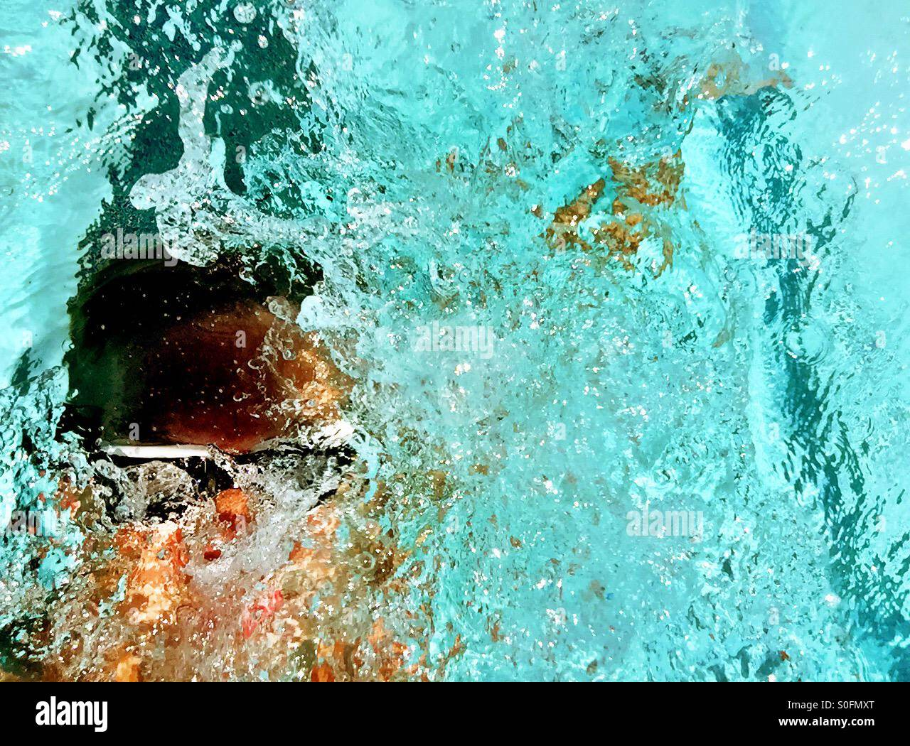 Closeup view above man swimming competition backstroke in an outdoor swimming pool. Sun glistening through wake - Stock Image