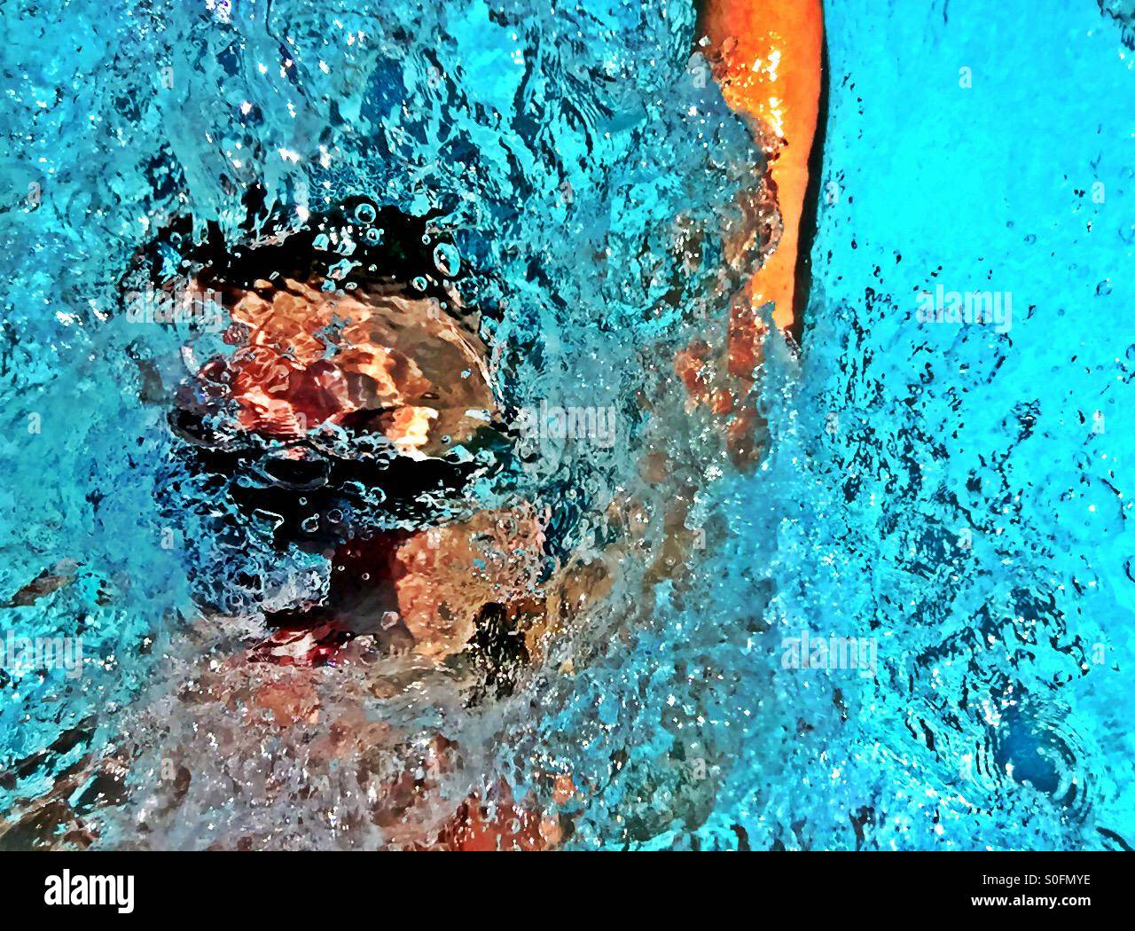 Closeup view above goggled man swimming competition backstroke inundated in wake of water splashes and bubbles. - Stock Image