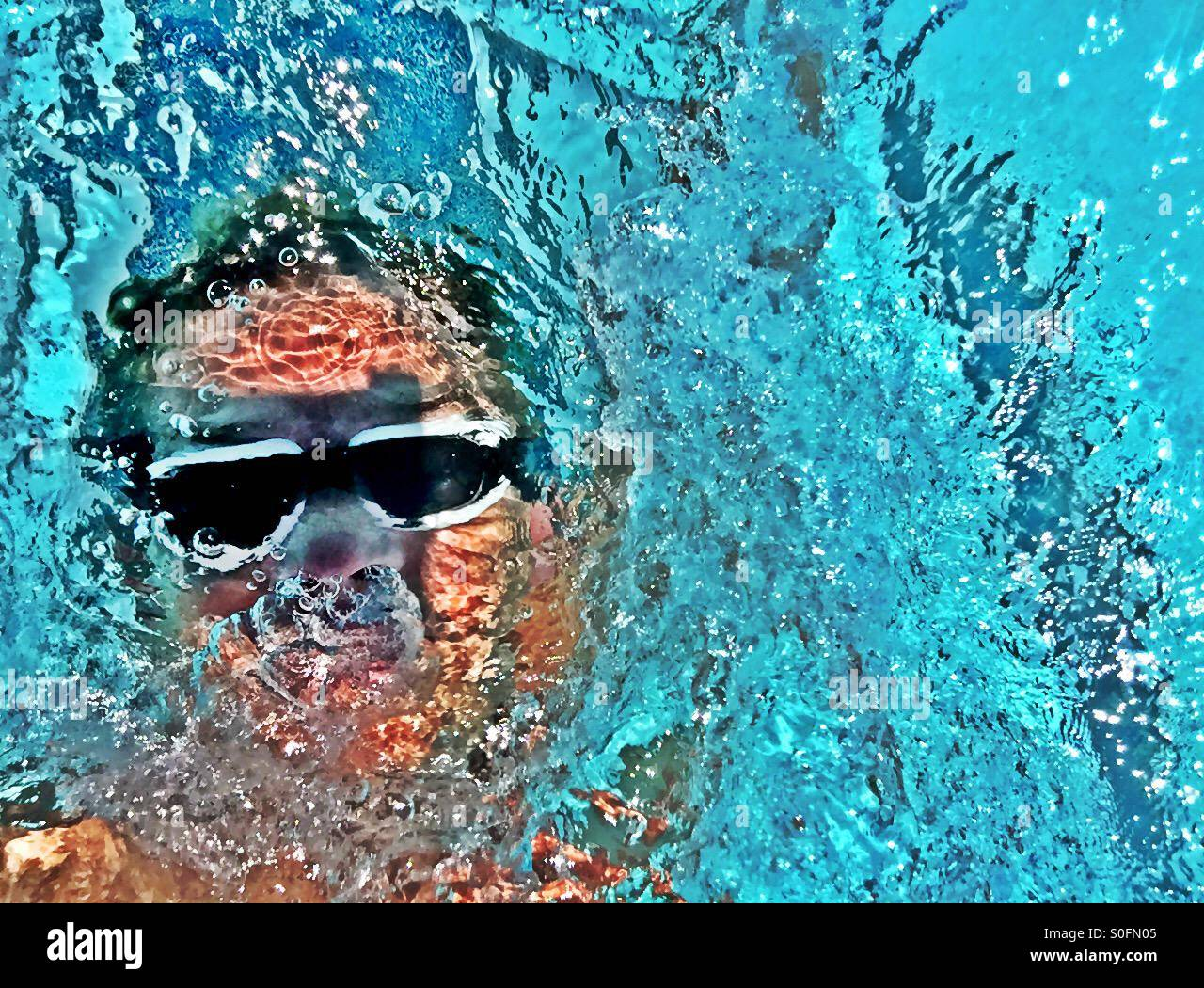Closeup view above male swimmer doing backstroke facing up in an outdoor swimming pool competition. Sunlit wake, - Stock Image