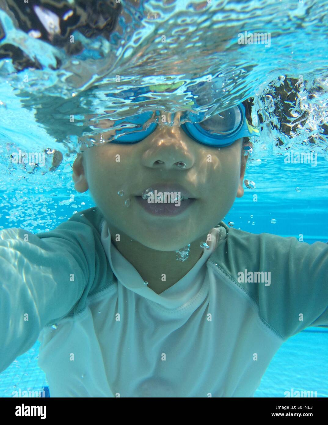 Underwater image of a young 5 year old Asian boy with half face submerged in water Stock Photo