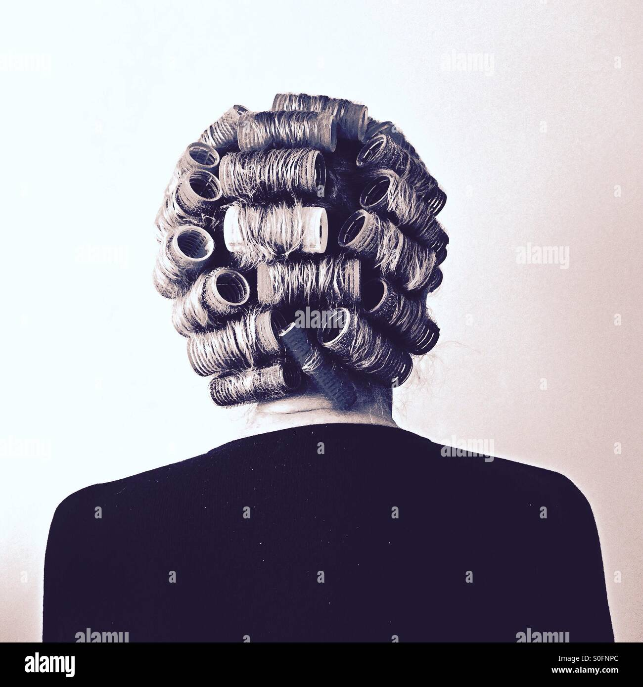 Senior person with hair rollers - Stock Image