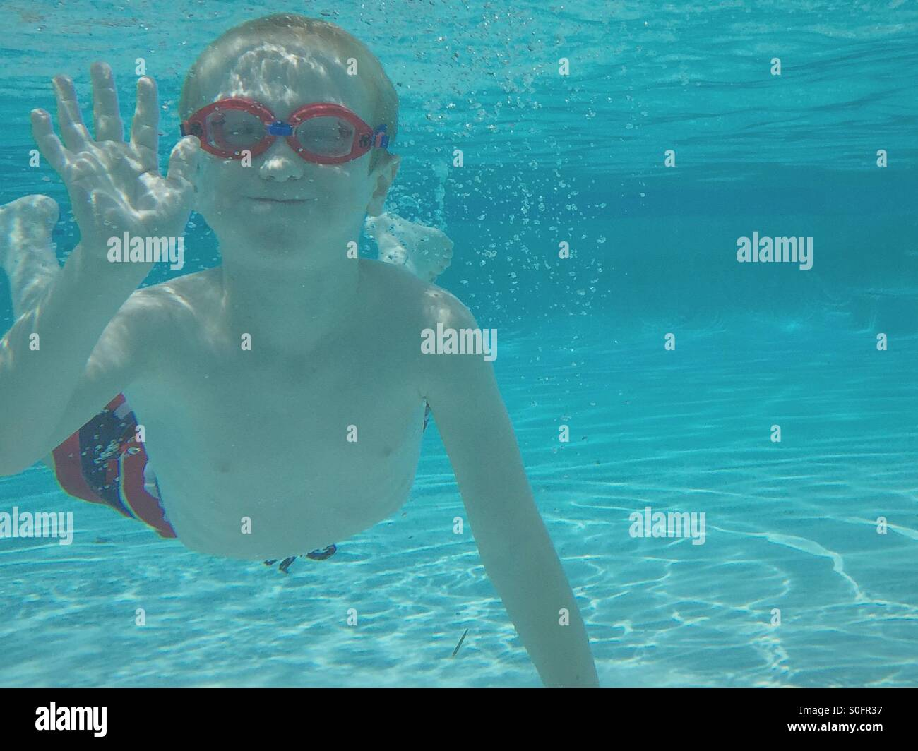 Young boy in swimsuit and goggles waving to the camera from under water. - Stock Image