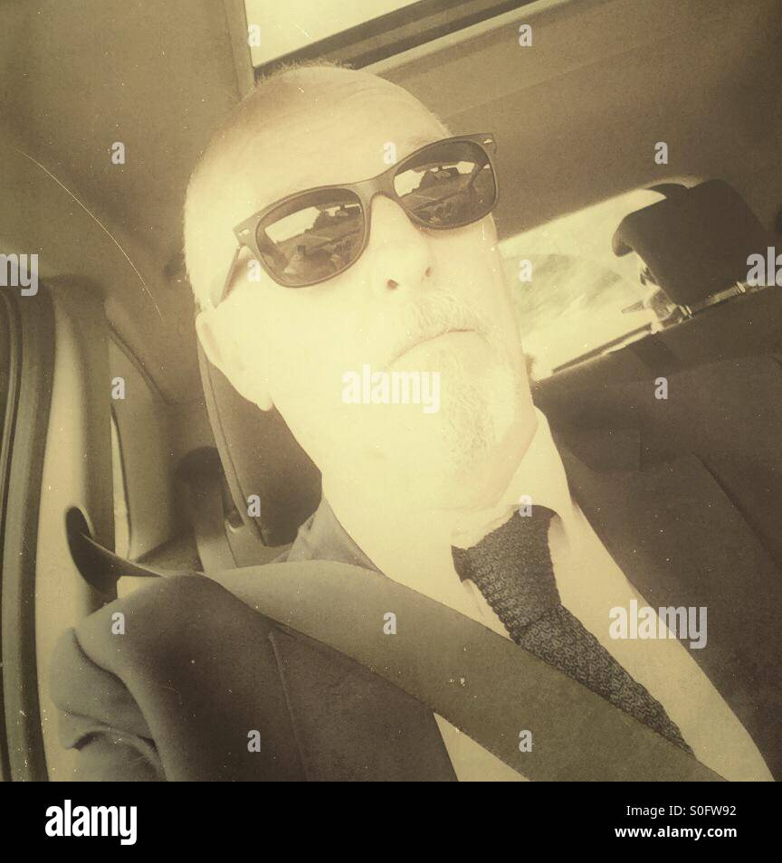 Middle aged male dressed in shirt and tie wearing a blazer and sunglasses sitting behind the wheel in the drivers - Stock Image