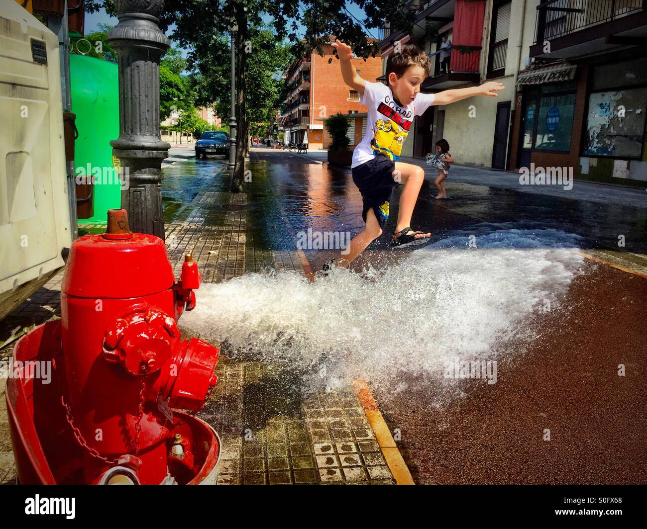 Summer fun- boy leaping over water hydrant stream - Stock Image