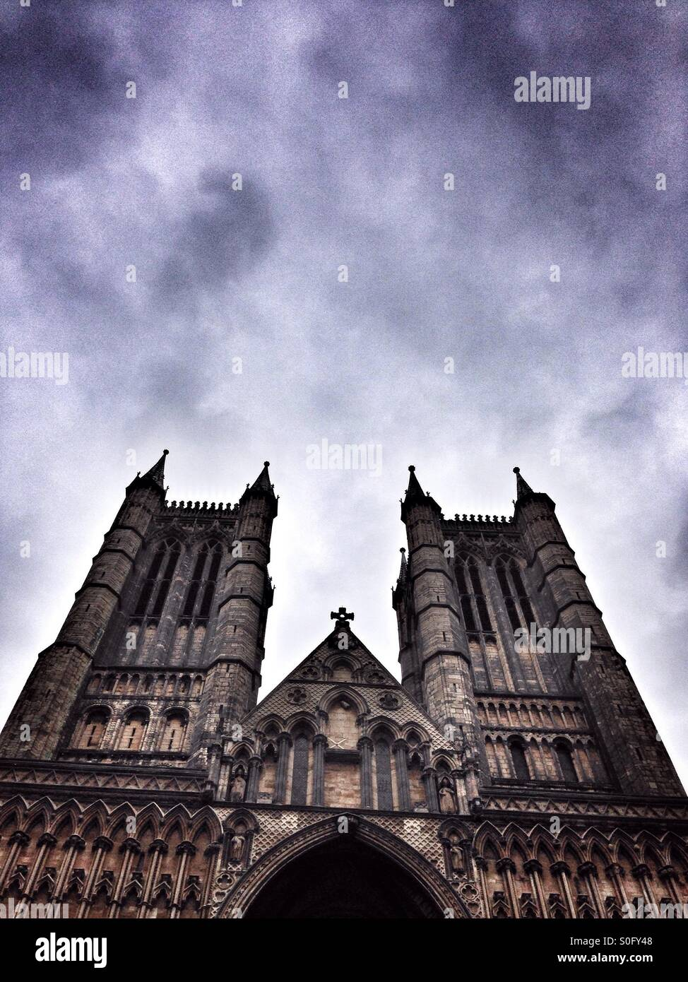 Lincoln Cathedral low angle view of the West facade towers. Lincolnshire, England, UK - Stock Image