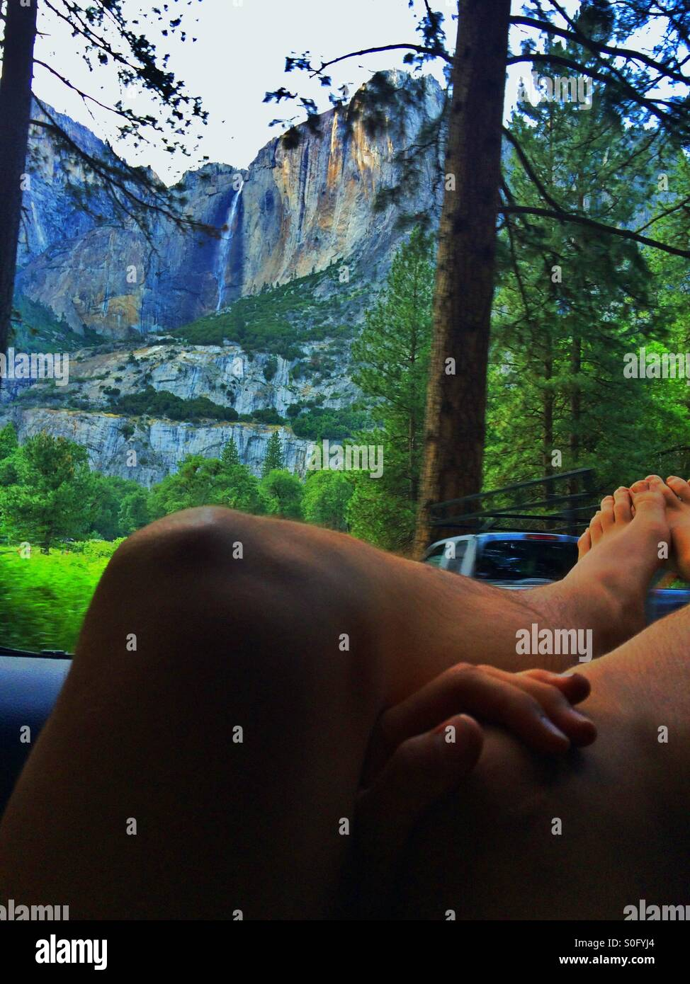 A young adult relaxes with his feet out the car window while gazing up at Yosemite Falls - Stock Image