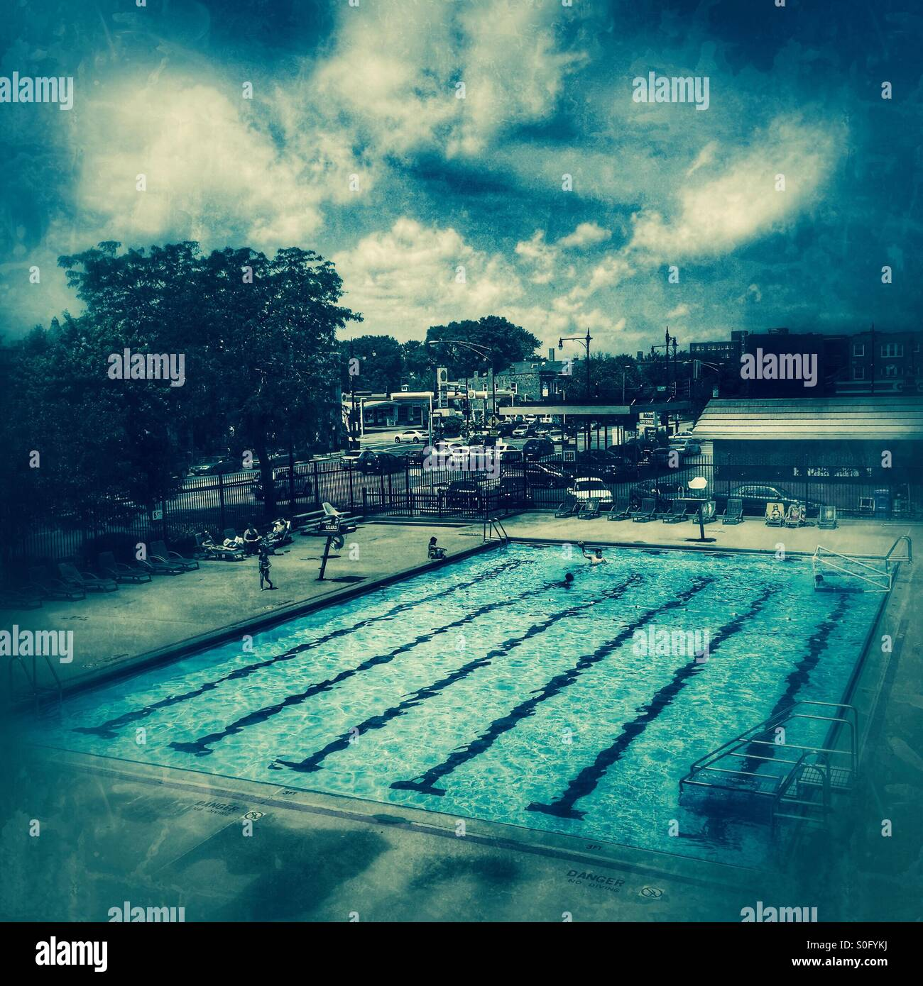 Swimming pool on a hot summer afternoon in the city. - Stock Image