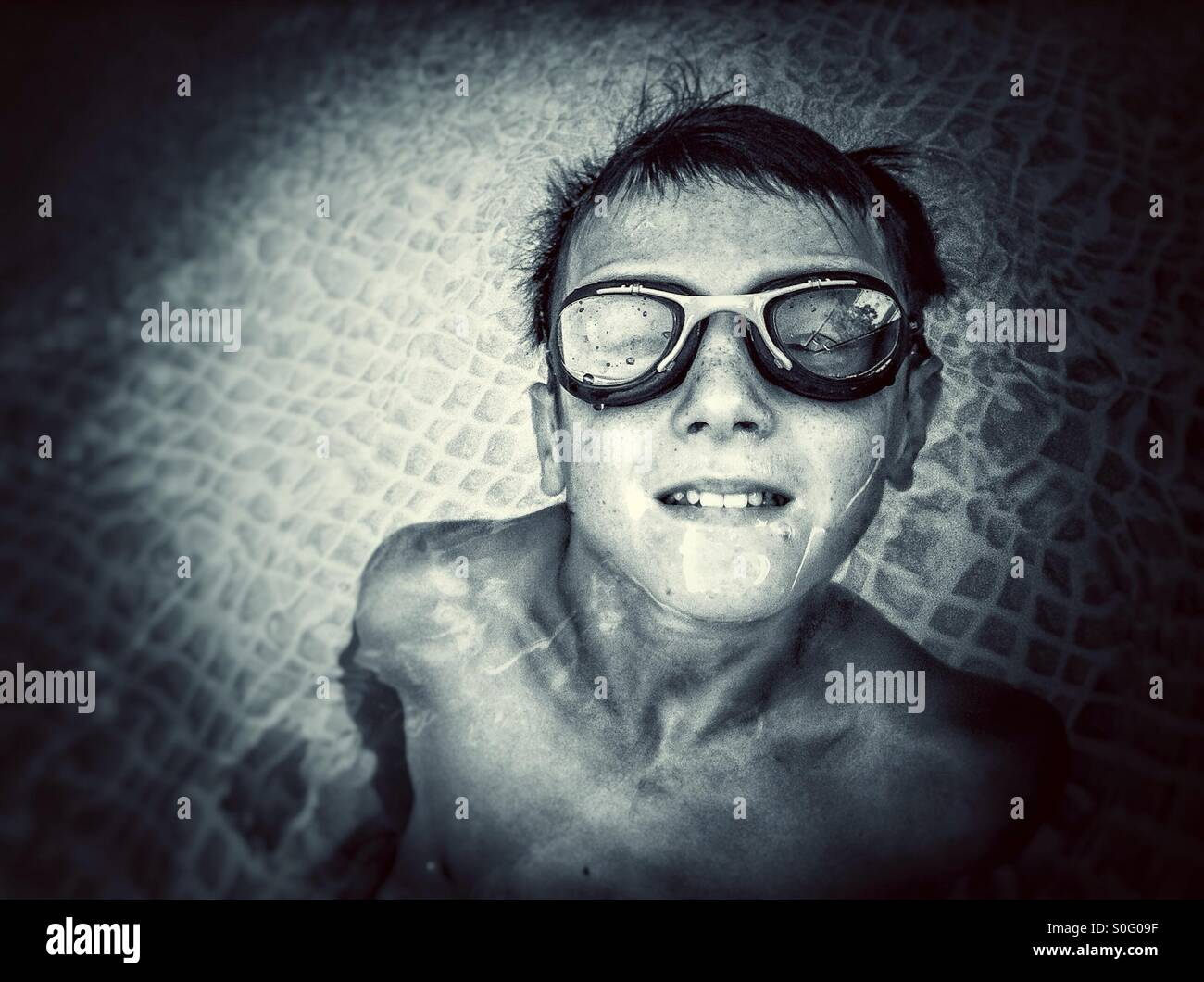 Boy with goggles looking at the camera inside a swimming pool Stock Photo