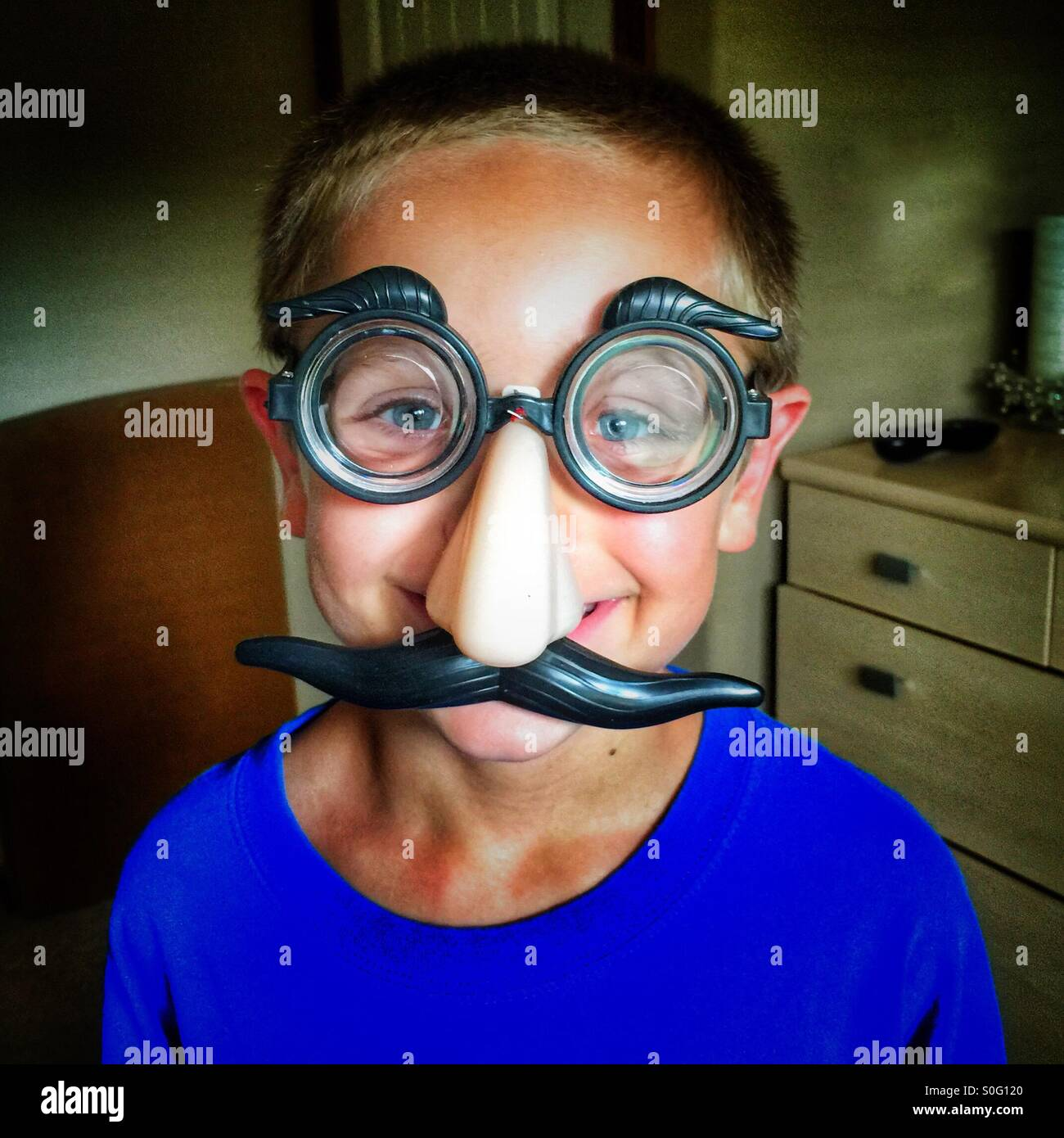 Young boy wearing a funny mask with glasses, nose, and a mustache - Stock Image