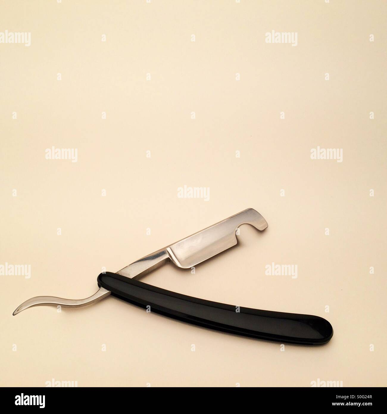 Manipulated image showing a cut throat razor with a notch taken out of it, plenty of room for copy space - Stock Image