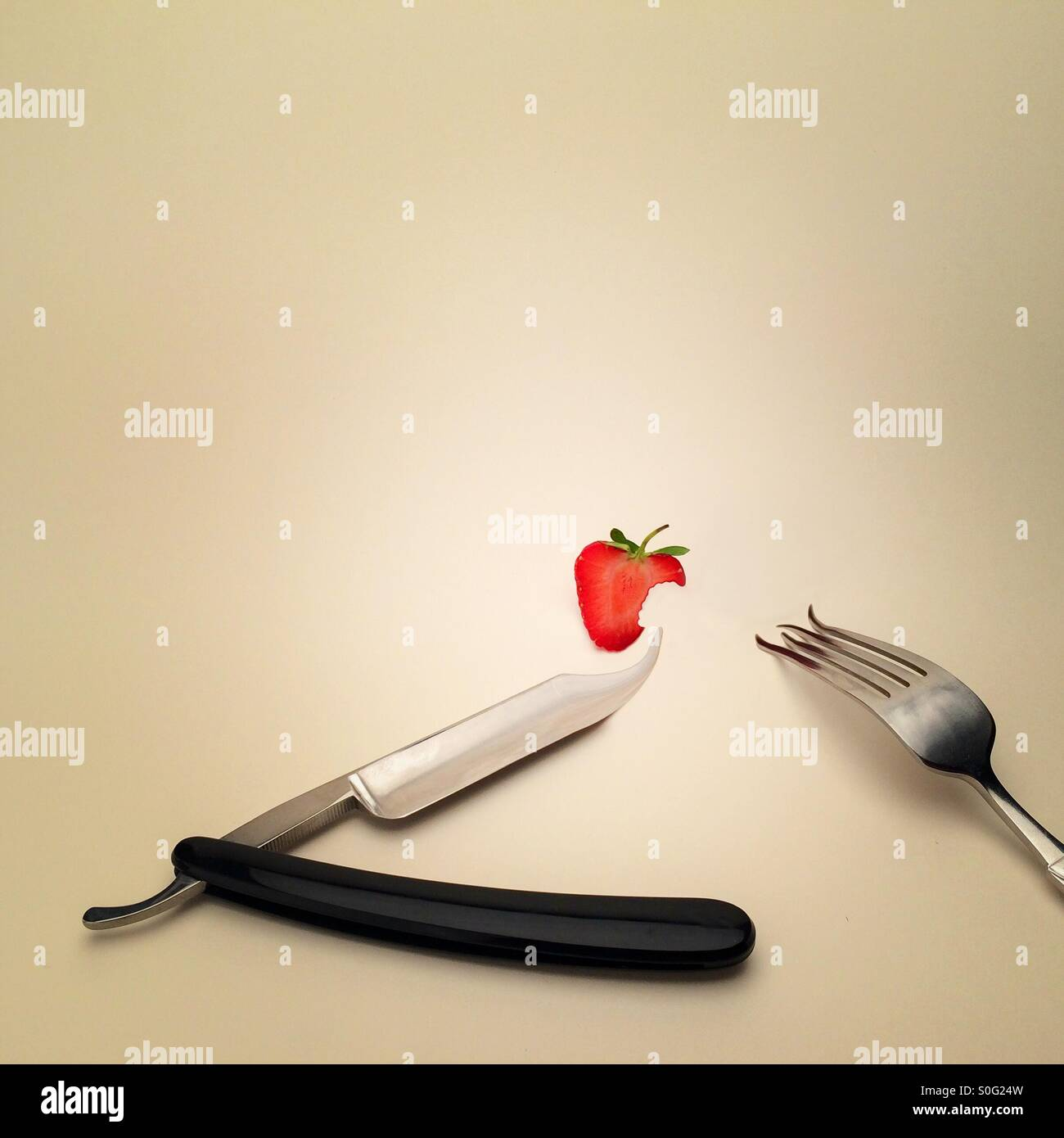 Cut throat razor knife fork and strawberry ( digitally manipulated image) showing a strange and surreal dinner place - Stock Image