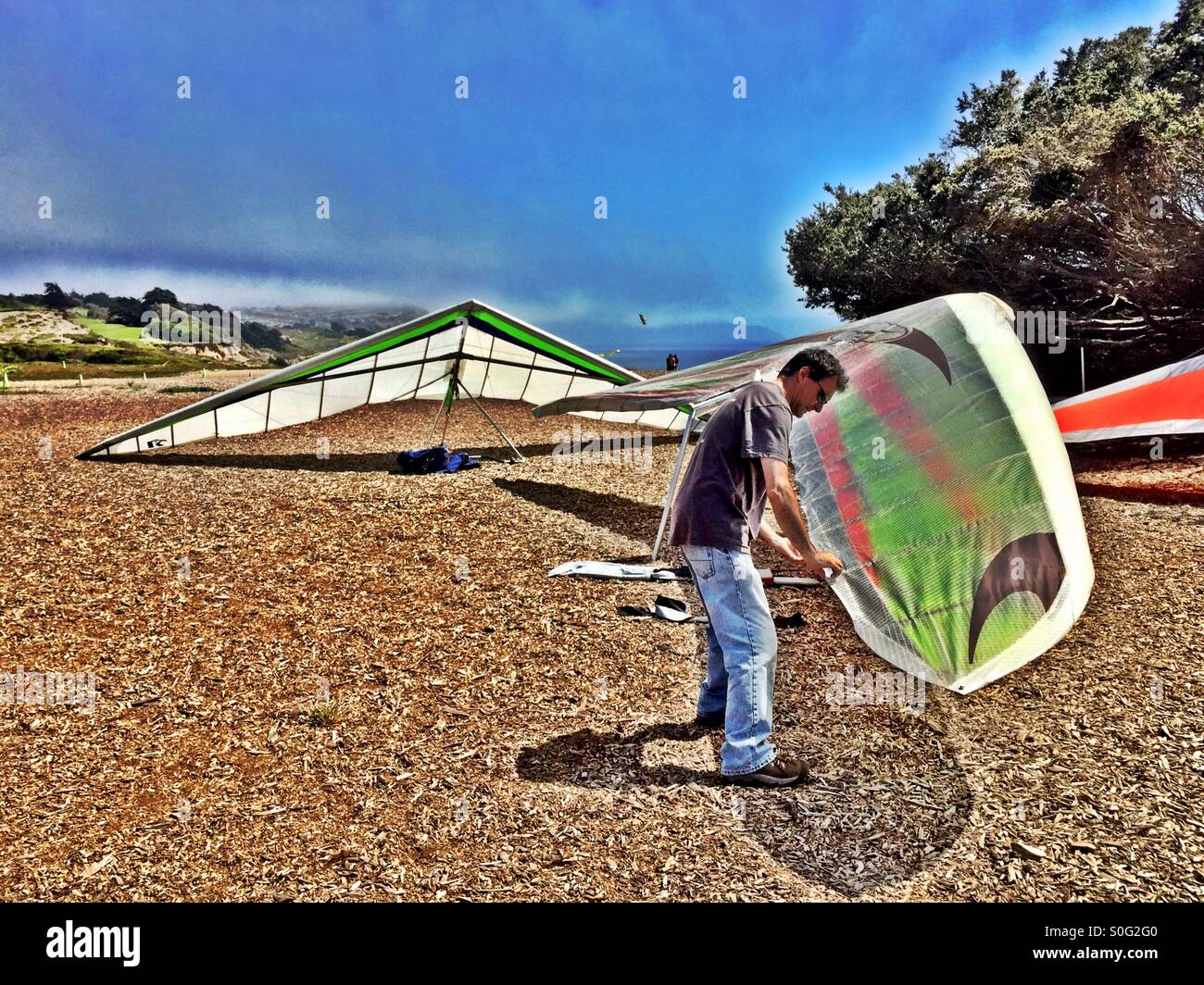 Hang gliding preflight check before takeoff atop the high sandy Fort Funston cliffs in San Francisco, California, - Stock Image