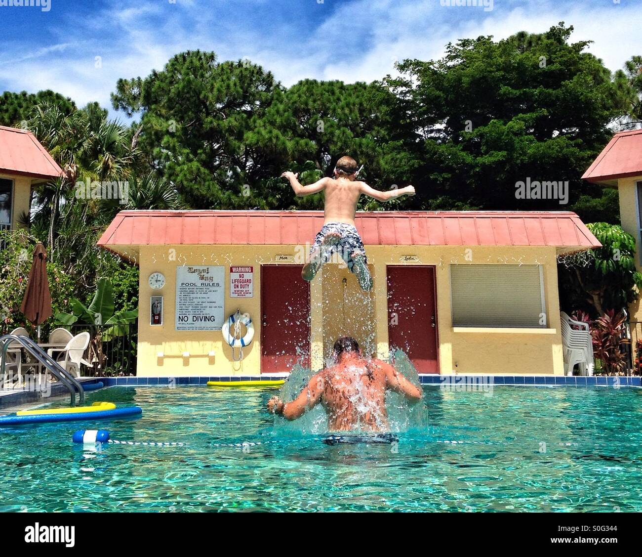 Child jumping off father's shoulders into a pool in Naples Florida - Stock Image