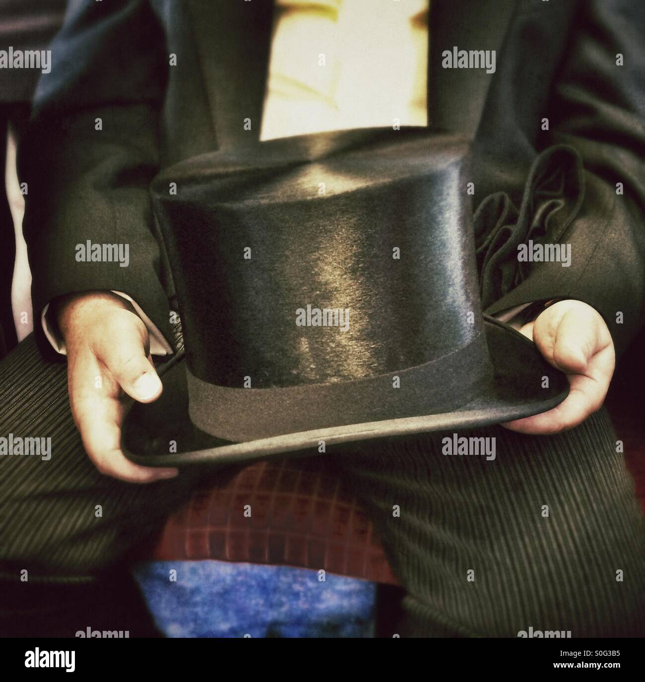 A man holding a top hat. - Stock Image