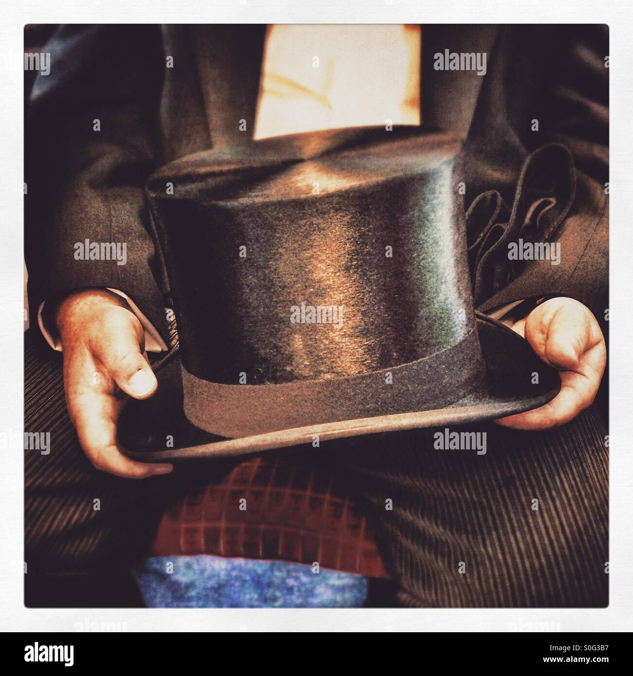 A man holding a top hat - Stock Image