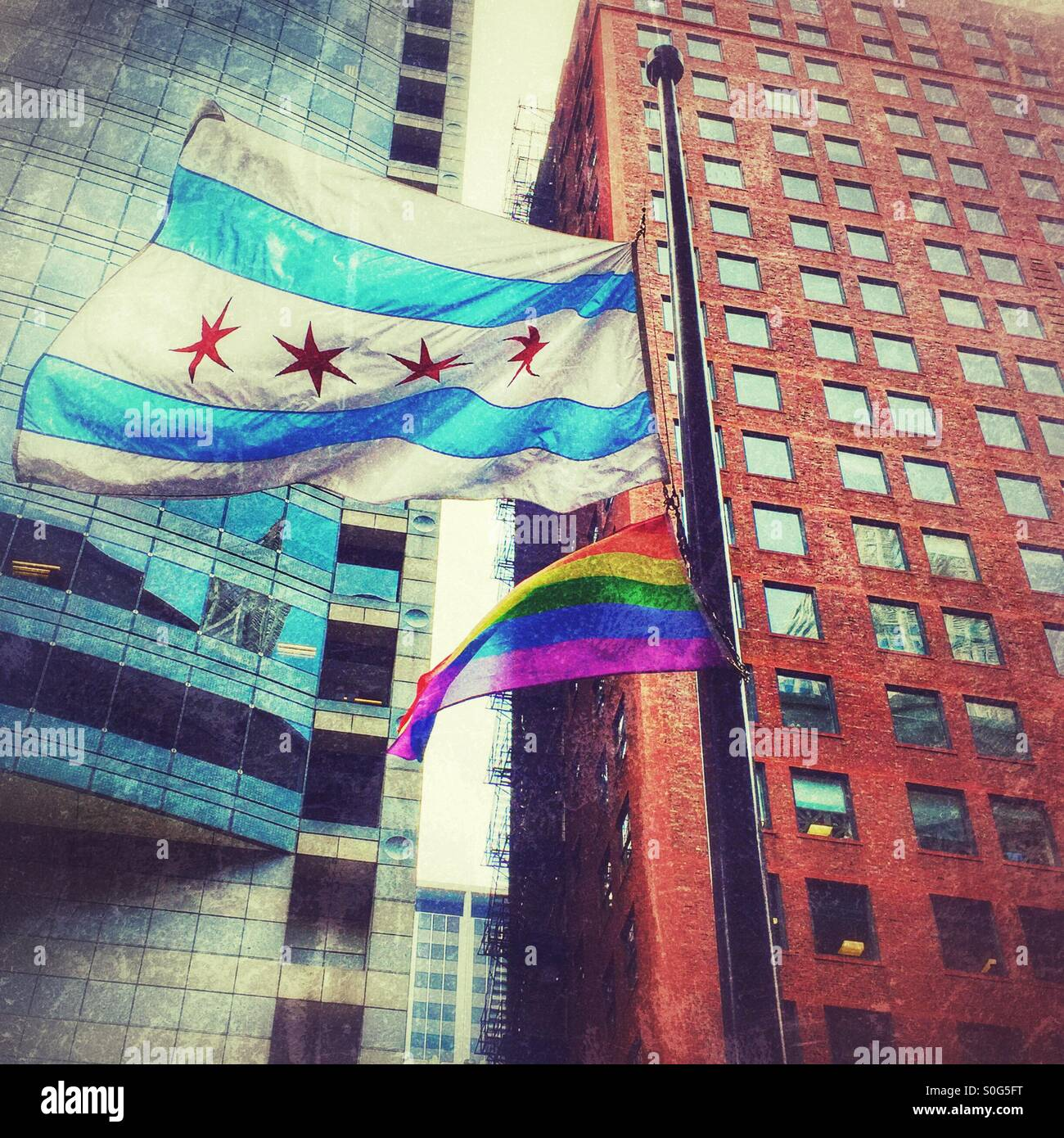 Pride flag waving along with Chicago flag in the Chicago Loop - Stock Image