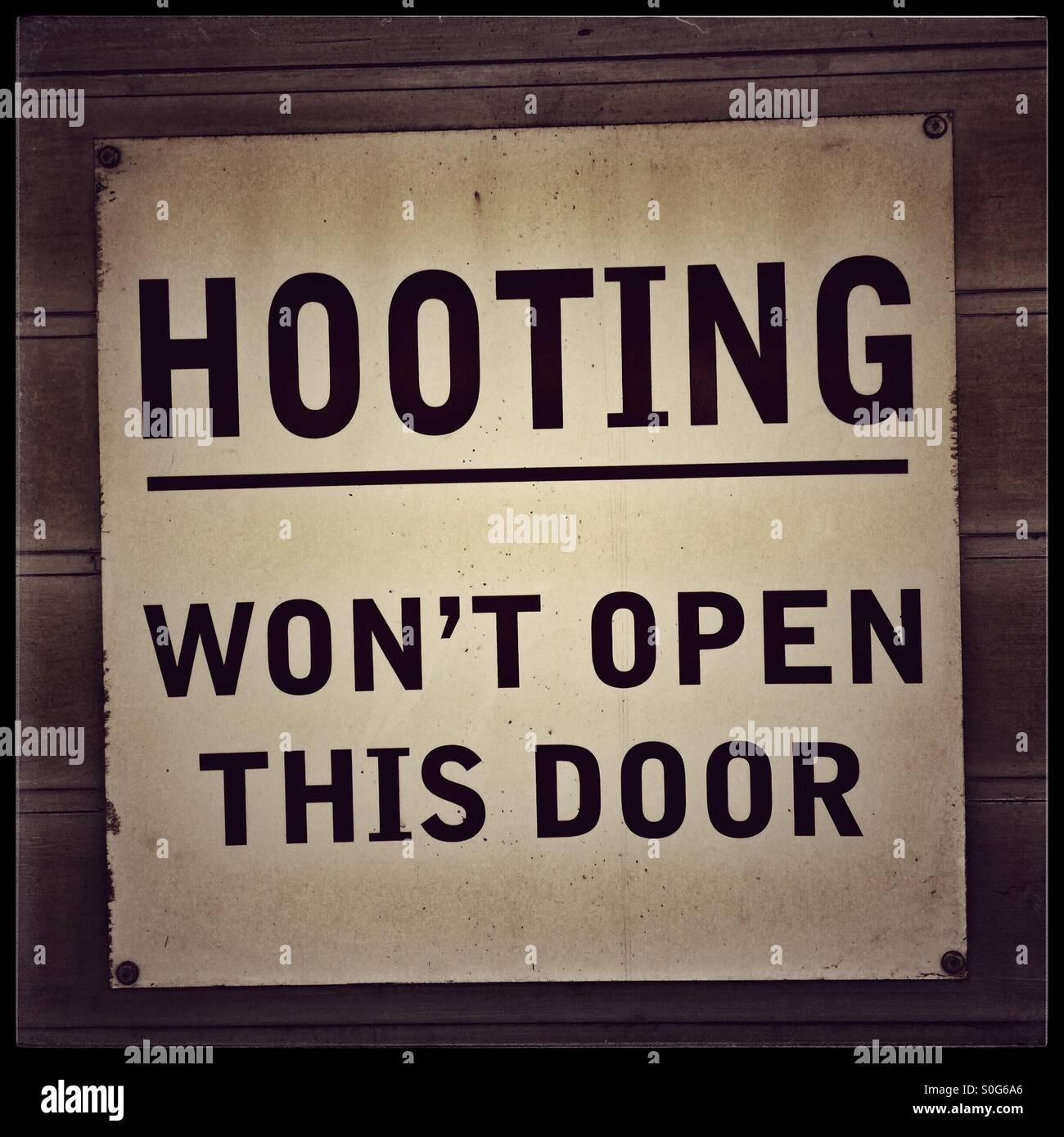 Humerous sign on garage door. - Stock Image