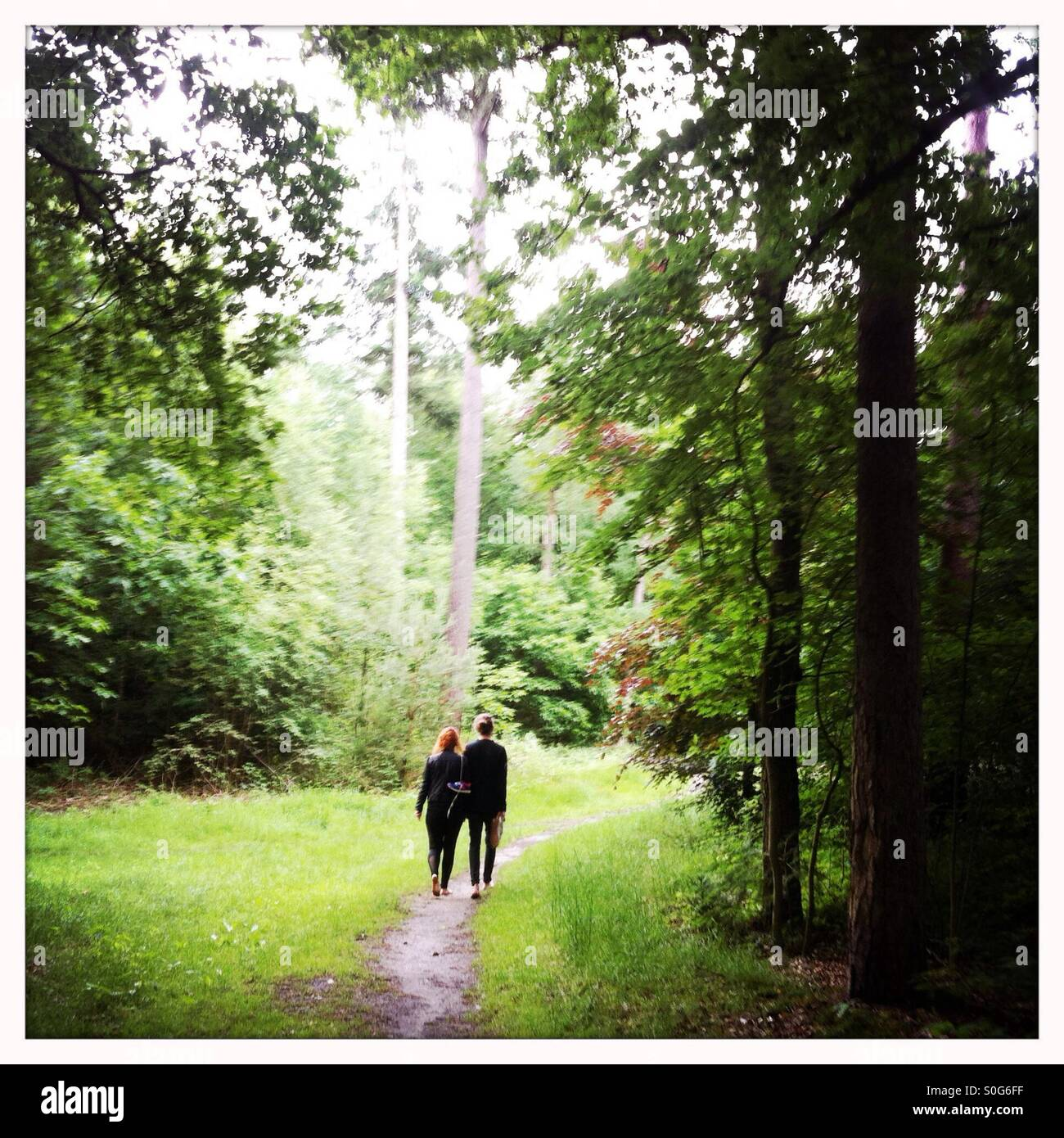 Boy and girl walking together in a forest on bare feet - Stock Image