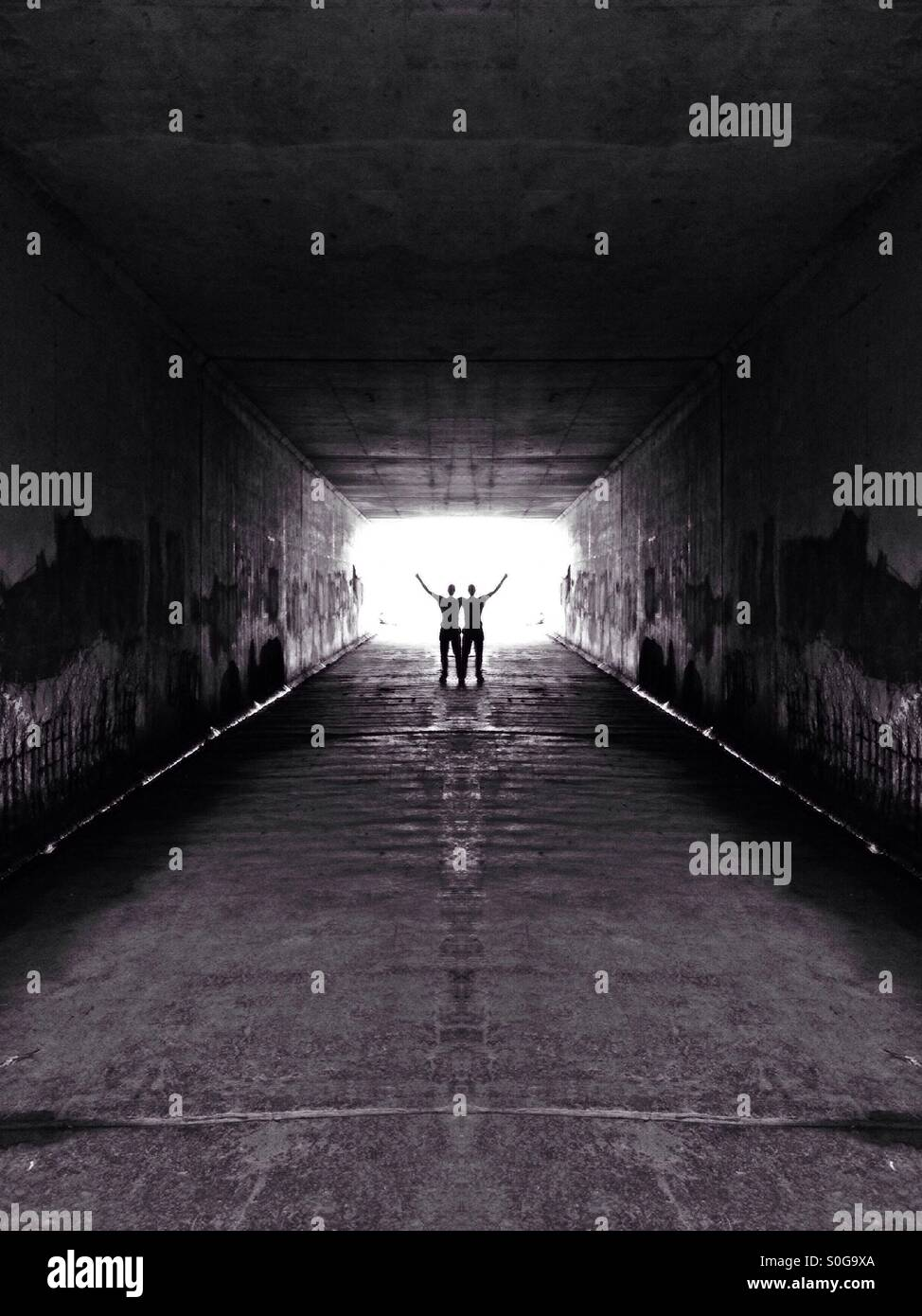Symmetrical image of a man stood at the end of a tunnel - Stock Image