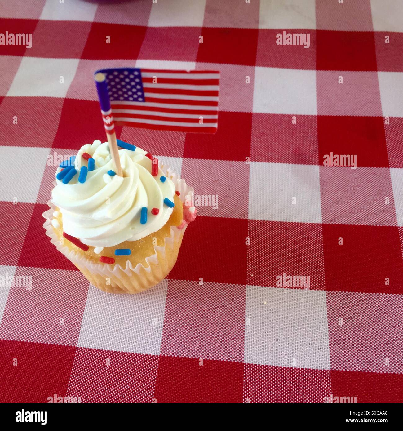 A cute white cupcake sprinkled with red white and blue sprinkles with an American flag sits on a checkered tablecloth. - Stock Image