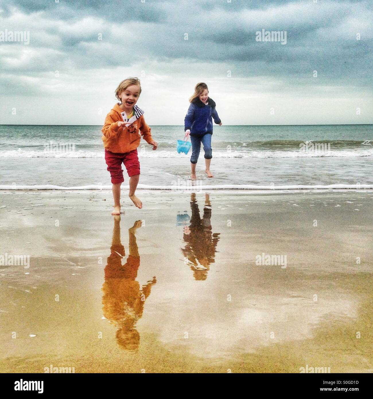 Wave dodging on Bournemouth beach - Stock Image