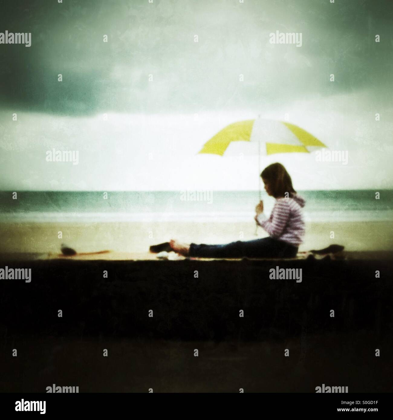 Girl sat on a wall with an umbrella - Stock Image