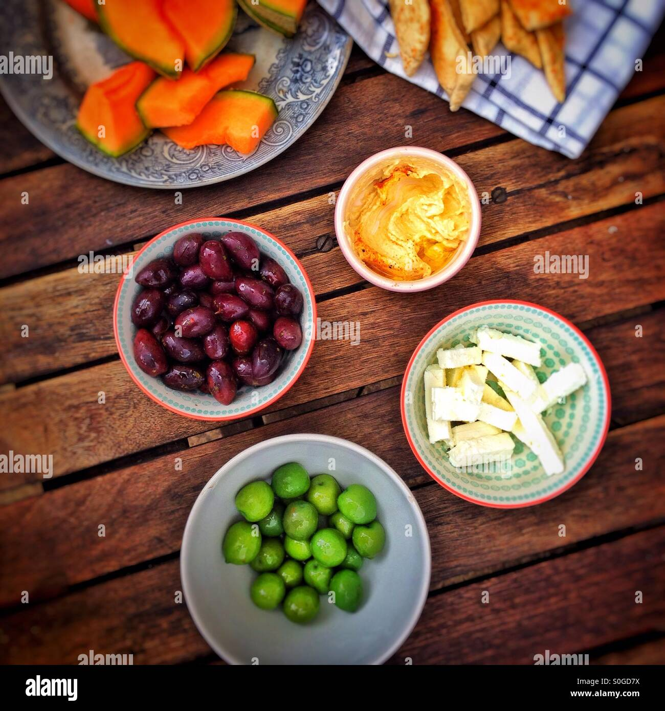 Olives, houmous, cheese and melon on a wooden table - Stock Image