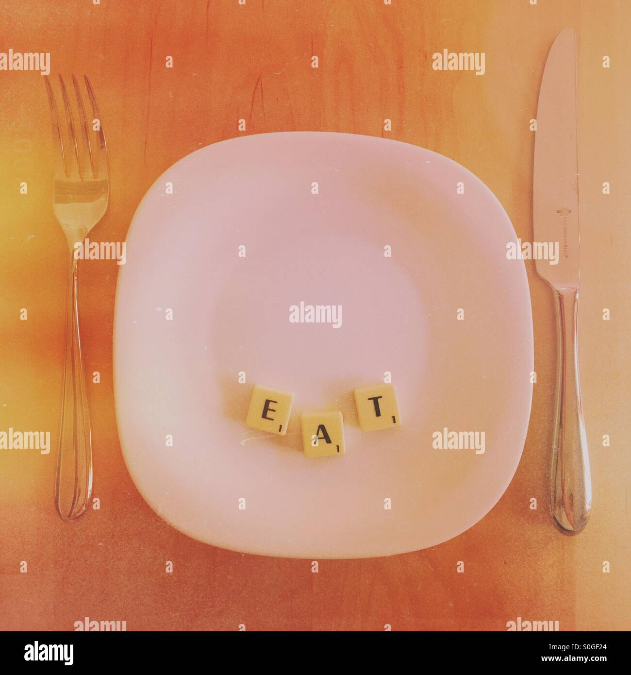 Plate with scrabble word EAT - Stock Image