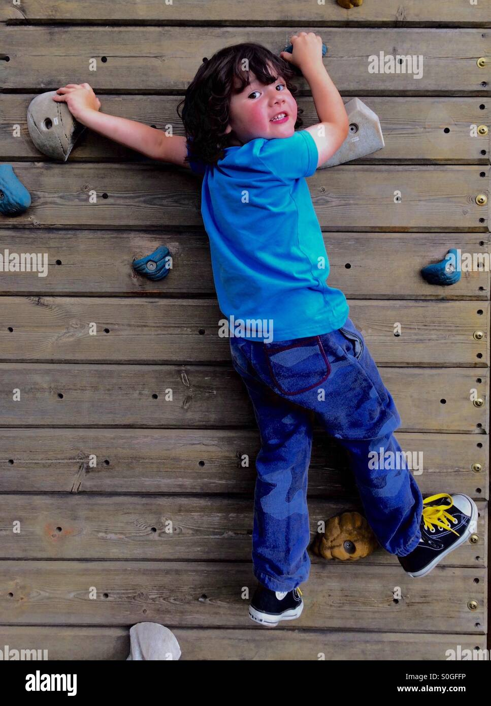Young boy 4 years old on climbing wall - Stock Image