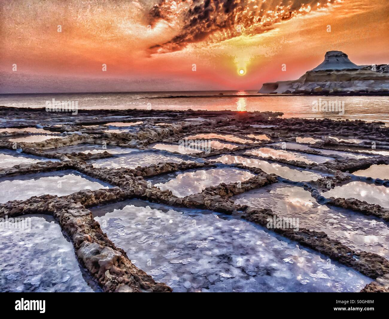 Dramatic sunrise over salt pans and calm sea - Stock Image