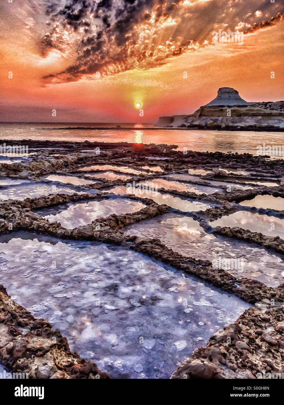 Dramatic dawn over calm bay and salt pans - Stock Image