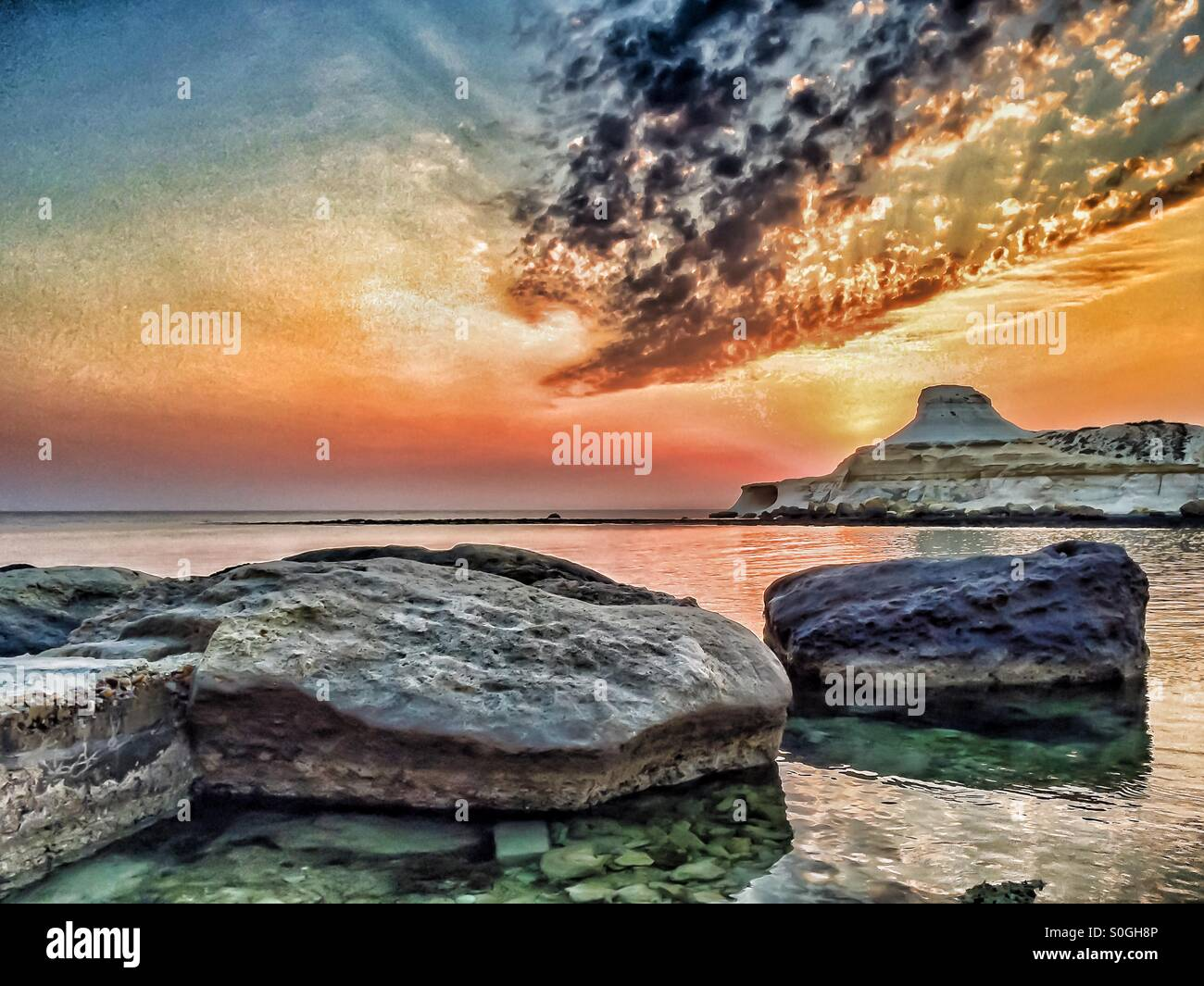 Dramatic sunrise over calm bay with rocks in the foreground - Stock Image