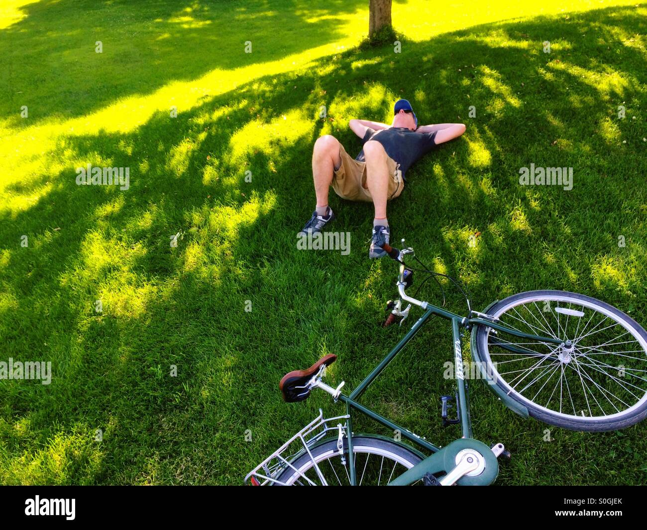 Man resting next to bike - Stock Image