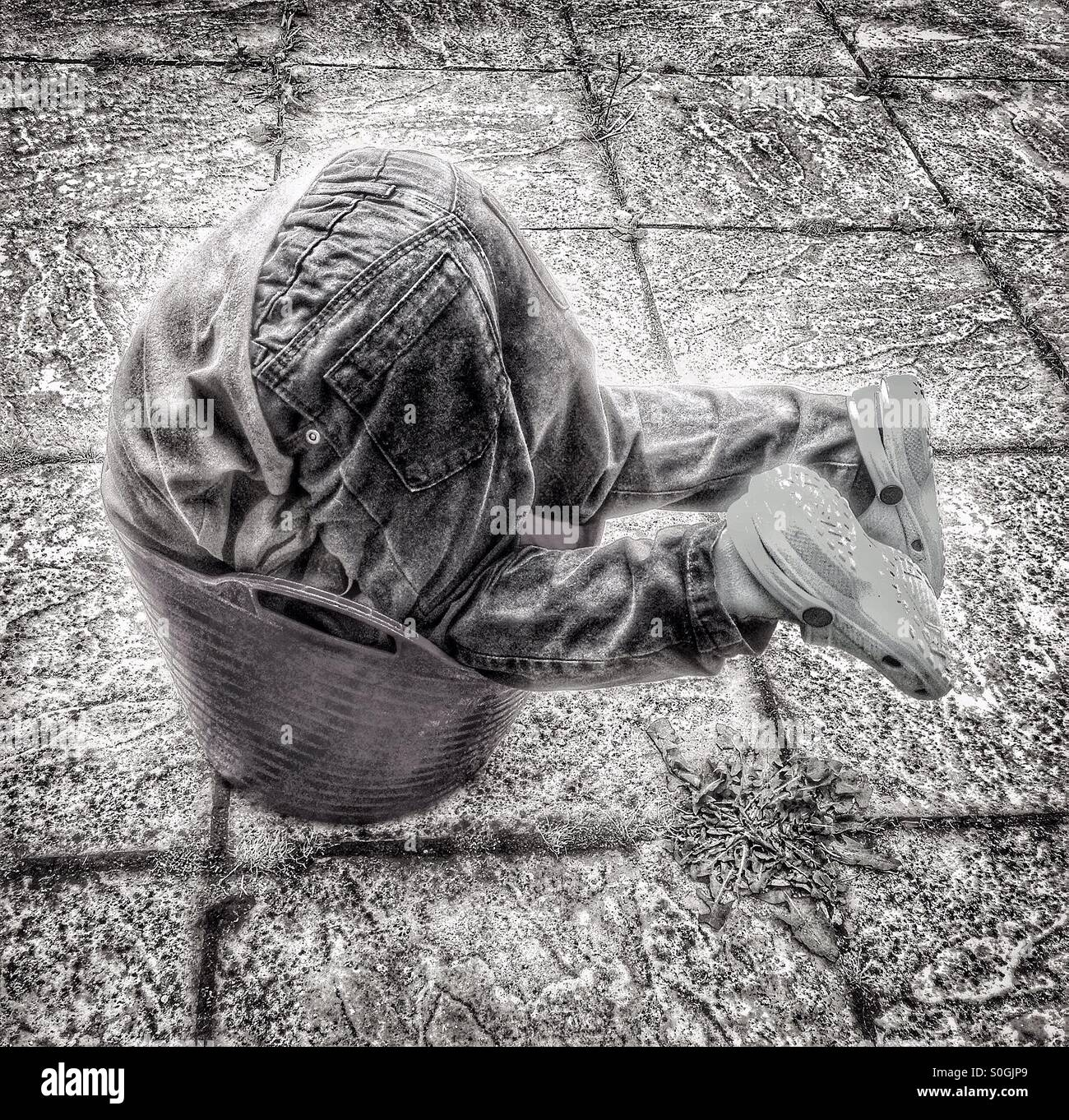 Child playing in a bucket. - Stock Image