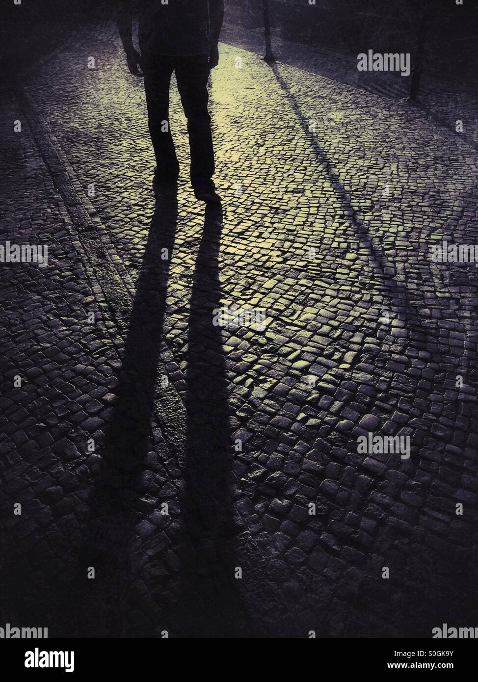 Shadowy male figure in the street - Stock Image