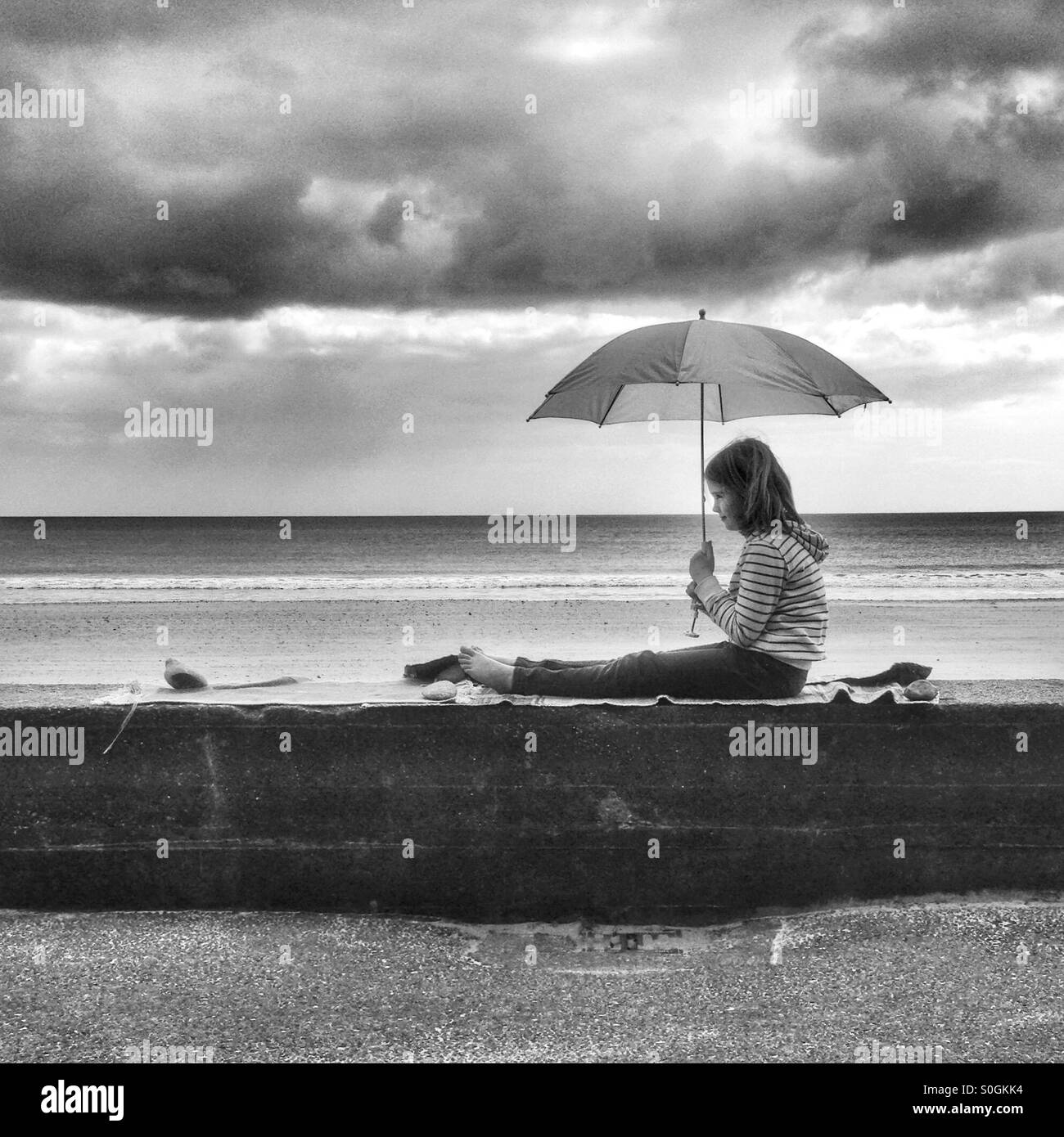 Girl sits on a beach wall with an umbrella - Stock Image