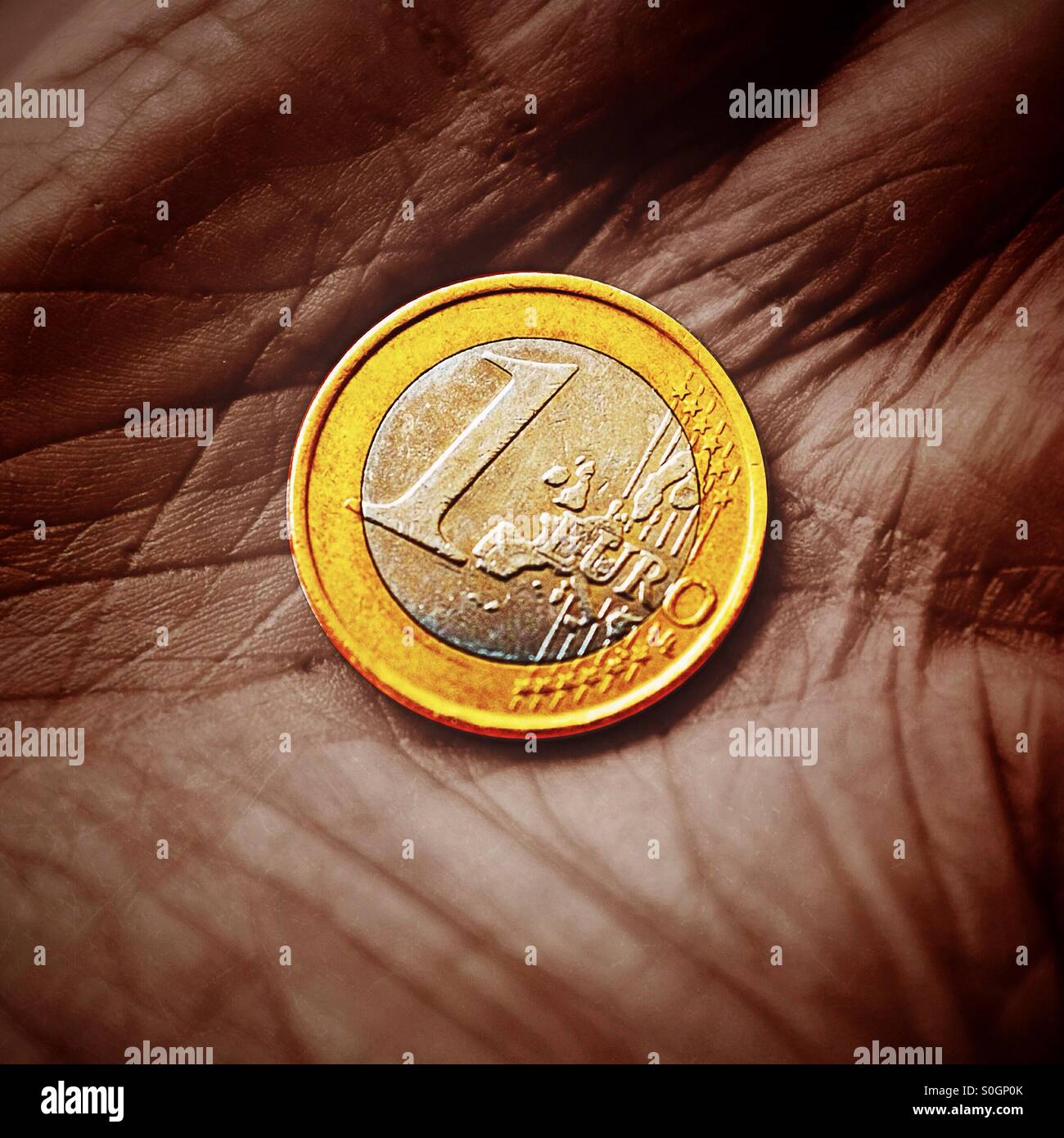 A close up of a Euro coin in a pensioner's hand - Stock Image