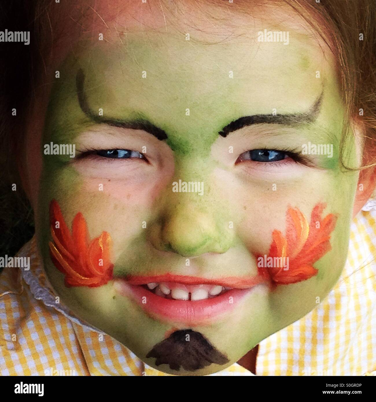 Child with face painted like an Eastern dragon - Stock Image