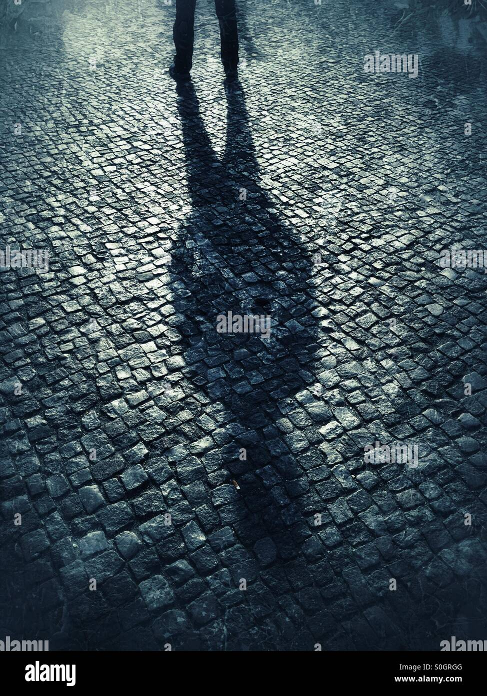 Sinister male shadow on cobbled road - Stock Image