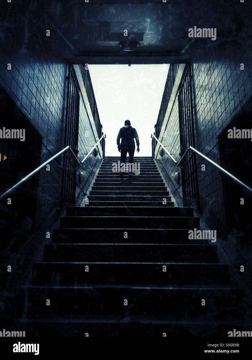 Man walking up the stairs - Stock Image