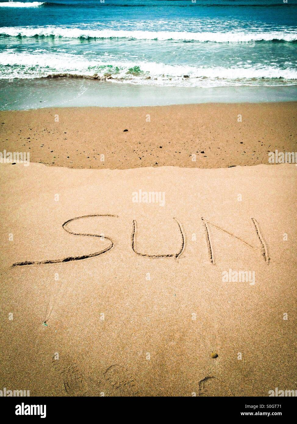 The word Sun written in the sand - Stock Image