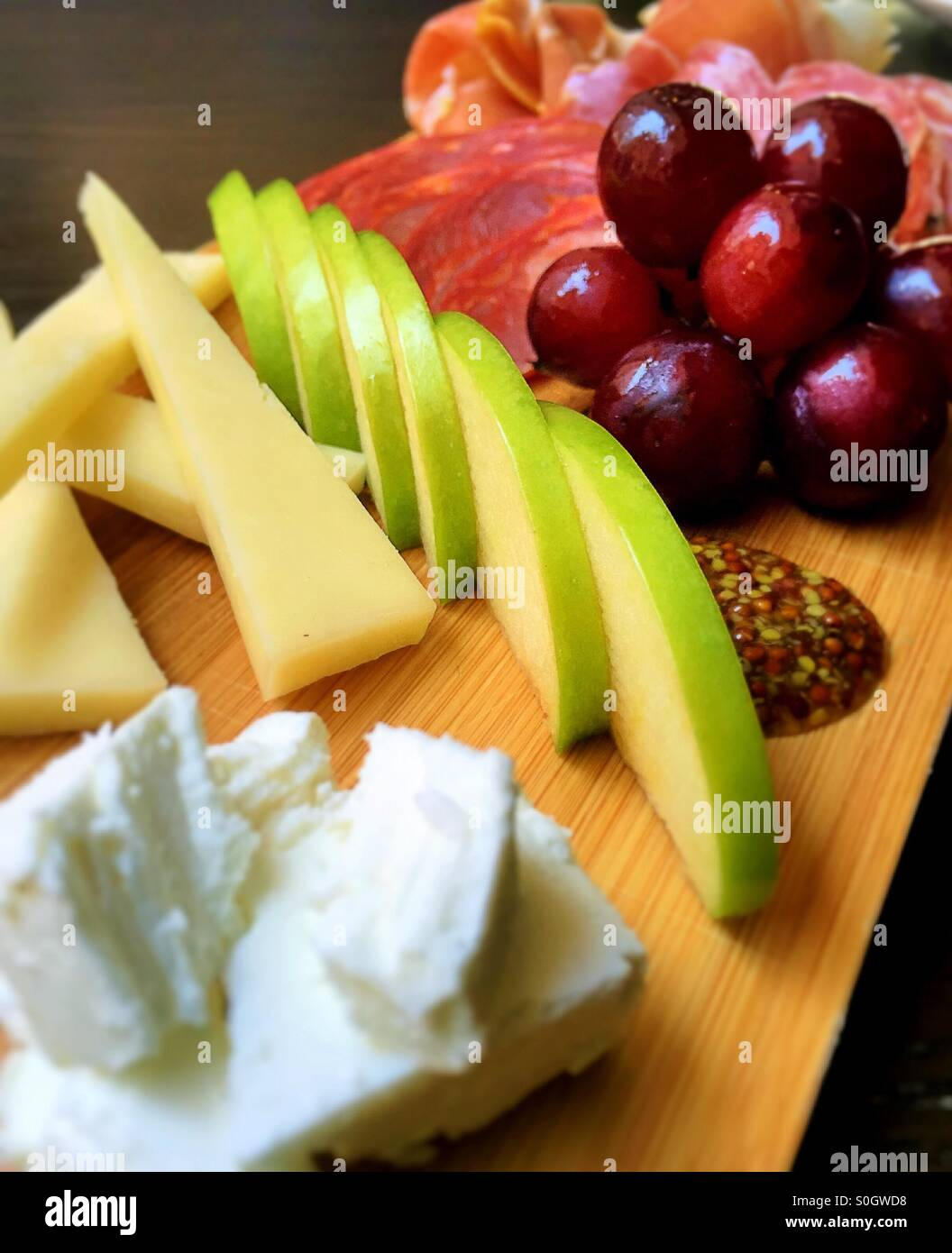 Charcuterie plate of fruit meat and cheese - Stock Image